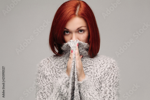 Fotografía  Studio portrait of young red haired unrecognizable woman wearing warm gray seater hiding face by hands
