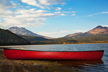 Empty Red Canoe On Lakeshore A...