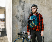 Cyclist Standing By Building Corner
