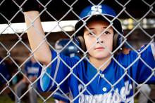 Baseball Player Wearing Helmet Standing Behind Chainlink Fence