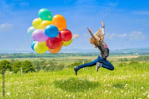 Fotografija  Glückliches Mädchen spring mit bunten Luftballons über eine grüne Wiese