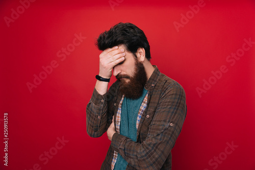 Fotografie, Tablou Close up portrait of disappointed stressed bearded young man in with closed eyes