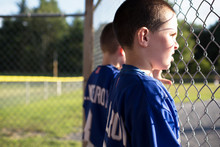 Side View Of Baseball Players Leaning On Chain Link Fence