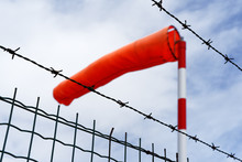 View From Below Of A Bright Red Bulging Windsock Of An Airfield Behind A Metal Fence With Barbed Wire, Blue Sky With Cloud Cover
