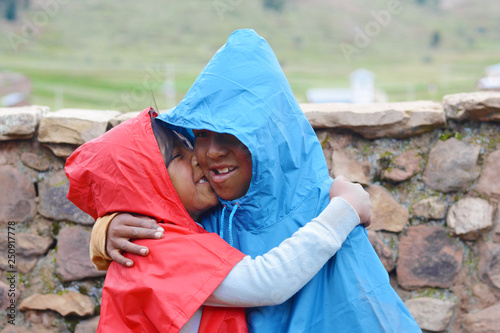 Fotografia  Happy native american kids wearing raincoat in the countryside.