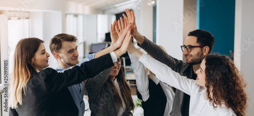Fototapety, obrazy: Smiling and laughing office working black and white men and women standing and giving high five to each other.
