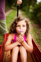 Girl (8-9) With Curly Hair Sitting In Red Basket And Holding Pink Flower Person In Background