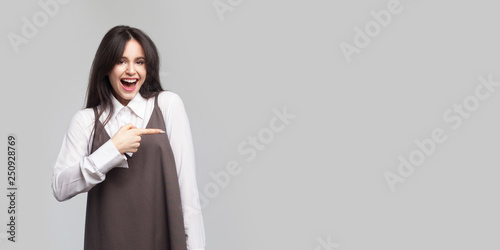 Fotografie, Obraz  Portrait of excited beautiful young woman in white shirt and brown apron, makeup, brunette hair standing, pointing at copyspace, looking at camera with surprised face
