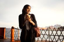 Brunette Female Wearing Black Jacket Standing On Ferry, Metal Fence, River In Background