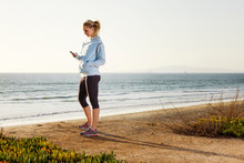 Woman Using Phone At Sunset On...