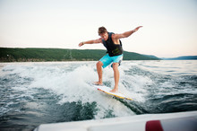 Young Man Wake Surfing On Lake