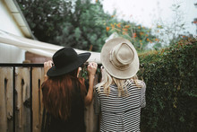 Rear View Of Two Young Women Looking Over Fence