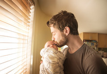 Father Kissing His Baby At Home