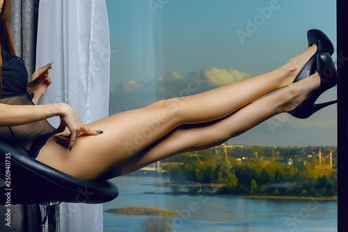 Fotografie, Obraz  Beautiful female legs with black heels  on blurred panoramic background of the city on the river