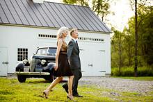 Glamorous Mature Couple Walking By Vintage Car