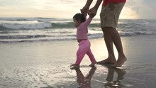 Portrait Of Little Girl Learn To Walk With Her Father In The Beach
