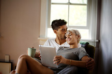Young Couple Sitting In Armchair Using Tablet Pc