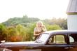 Glamorous mature woman posing behind vintage car