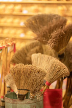 A Pile Of Bamboo Brooms In Market For Sale. Background For Texture