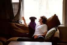 Young Man Sitting On Sofa With Dog And Looking Through Window