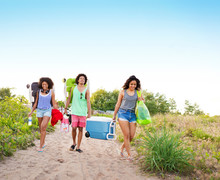 Teenage Girl (16-17) Carrying Cooler With Her Friends
