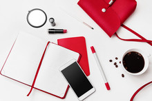 White Office Desk With Red Things, Blank Diary Or Planner, Pen, Phone Cosmetics And Cup Of Coffee. Business Woman Accessories