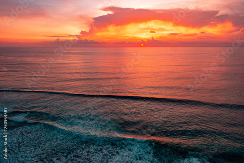 Foto auf Leinwand Koralle amazing scarlet sunset wuth a big clouds on beautiful tropical Bali beach