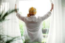 Rear View Of Woman Opening Curtains