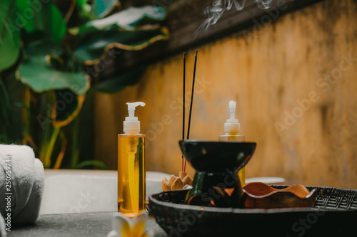 La pose en embrasure Spa Outdoor spa salon. Massage oils, burning incense sticks with smoke, towels, flowers on wooden stone table. Bath, green leaves on background