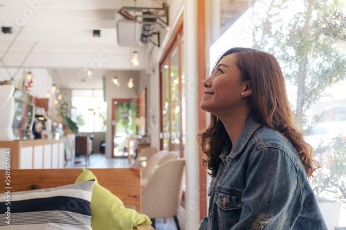 Foto op Plexiglas Bakkerij A beautiful asian woman sitting in cafe with feeling happy