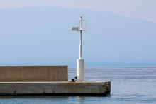 White Metal Pole With Light Beacon Acting As Local Lighthouse Powered With Small Solar Panel On Edge Of Stone Tiles Pier Surrounded With Calm Blue Sea On Warm Sunny Day