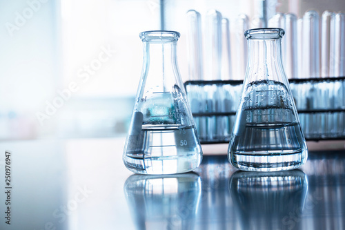 Photo  two clear flask with water in front of test tube in education chemistry science