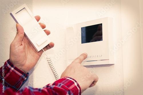 Fotografie, Obraz  man pressing the intercom with floor video