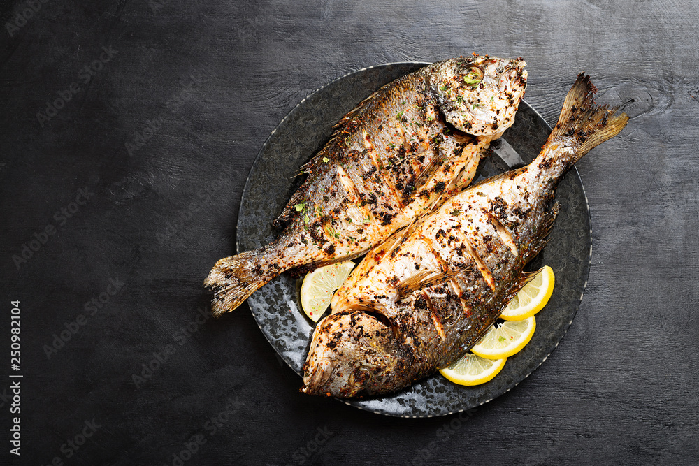 Fototapety, obrazy: Tasty grilled fish dorado with  lemon on kitchen table.