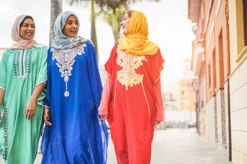 Foto op Aluminium Abu Dhabi Happy arabic friends walking in city center - Young arabian women having fun together on sunny day - Friendship, youth, ethnic culture and religion dress concept - Focus on center girl face