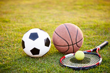 Football Basketball And Tennis Ball And Racket On Grass