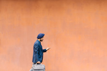 Indian Businessman Walking At Typing On His Cell Phone.