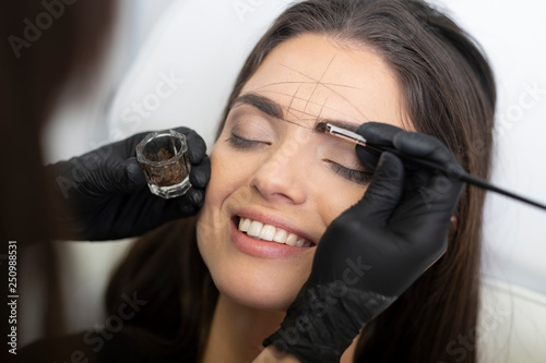 Fotografia Beautician in the saloon doing the perfect architecture of eyebrows