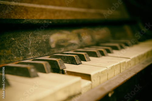 Old abandoned piano covered by dust. close-up at keyboard. - 250989106