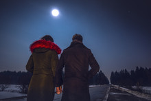 Young Couple Watching Beautiful Starry Sky On Full Moon Night.
