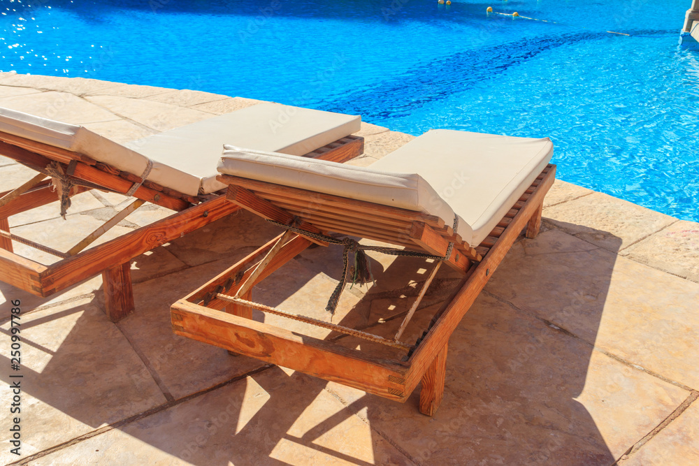 Fototapeta Chaise longues near a swimming pool. Concept of spa, rest, relaxation, holidays, resort
