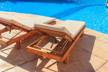 Chaise Longues Near A Swimming...