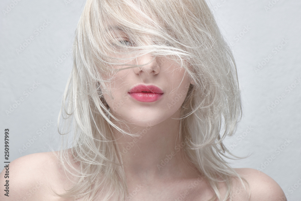 Fototapeta Portrait of a young beautiful blonde woman with plump red lips and bare shoulders on a white background close up. Fashionable fancy hairstyle