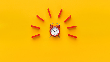 Alarm clock with red dominoes on yellow background