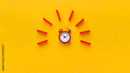 Photo Alarm clock with red dominoes on yellow background