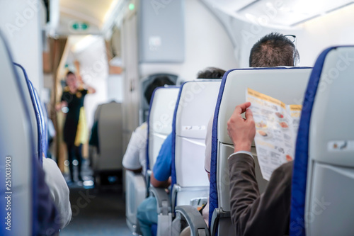 somebody read the menu in the plane, ready order to air hostess. Canvas Print