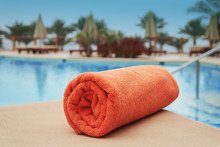 Orange Towel Lying On A Lounger Near The Swimming Hotel Pool Summer