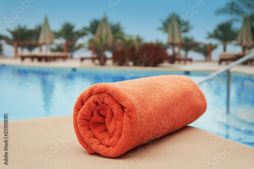 Fényképezés Orange towel lying on a lounger near the swimming hotel pool summer