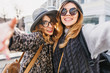 canvas print picture - Selfie portrait of joyful fashionable girls having fun on sunny street in city. Stylish look, wearing sunglasses, having fun, travelling with friends, smiling, expressing true positive emotions