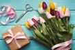 Colorful tulips bouquet and gift box on blue wooden background